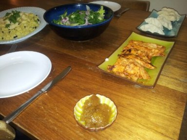 Image of a table with plates of tandoori chicken, pappadums, indian rice and salad on it