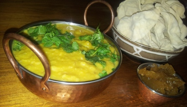 Picture of pumpkin and lentil soup in a bowl, next to pappadums and mango chutney